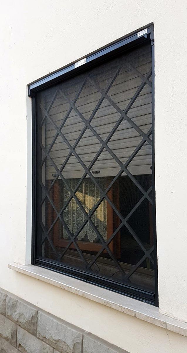 Zanzariera per finestra con apertura verticale abbinata ad una grata